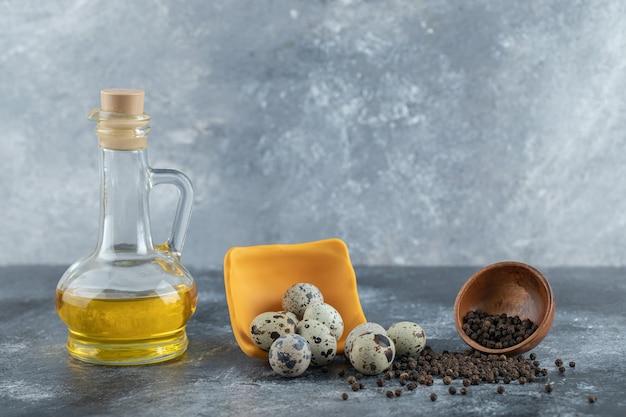 Куча перепелиных яиц на сером фоне с маслом и специями