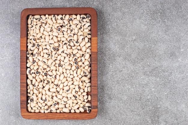 Куча сырых бобов на деревянной тарелке
