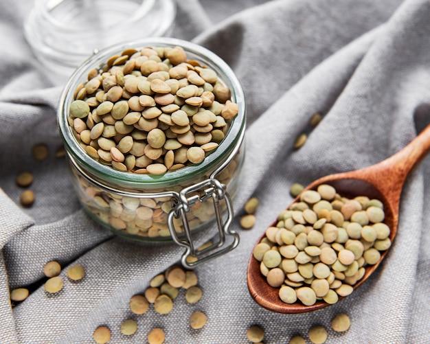 테이블에 유리 항아리에 원시 렌즈 콩의 더미
