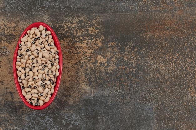 赤いボウルに生の白豆の山。
