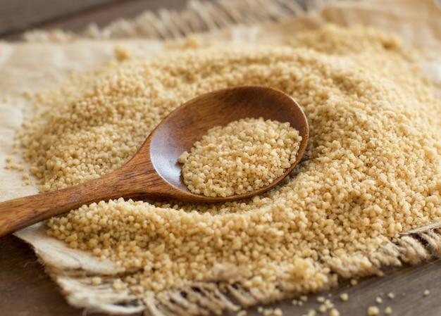 Куча сырой цельной пшеницы кускус с ложкой крупным планом