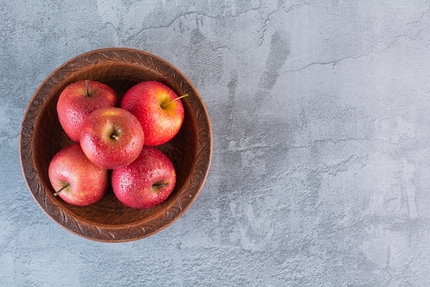 Куча красных яблок в шаре над серым.