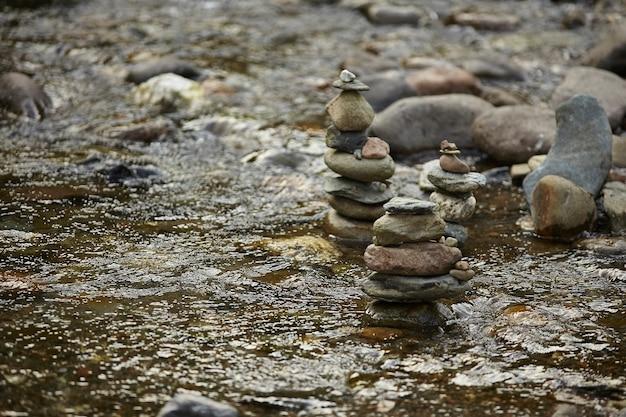 特定の波紋を作成する透明な水で小川の真ん中に岩の山。