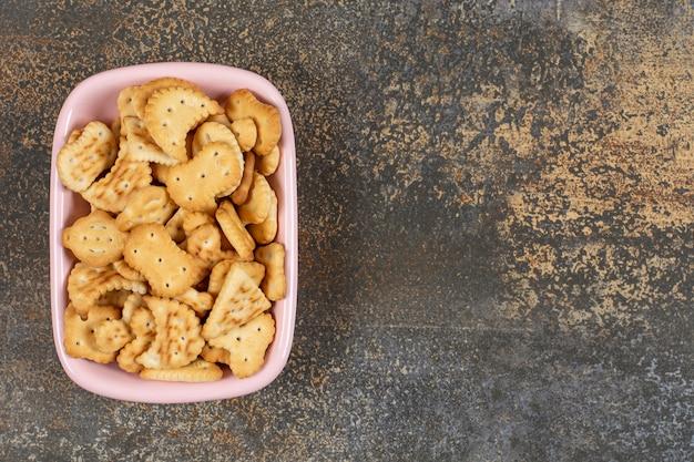 분홍색 그릇에 소금에 절인 크래커 더미입니다.