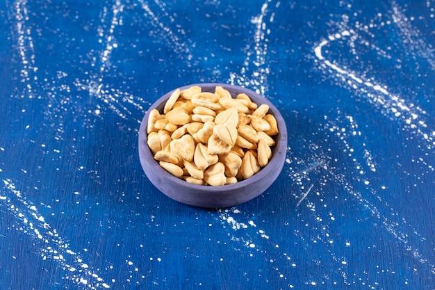 파란색 그릇에 소금에 절인 하트 모양의 크래커 더미.