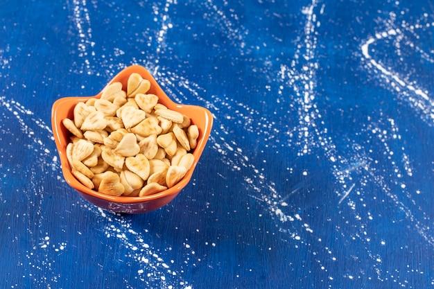 オレンジボウルに置かれた塩味のハート型クラッカーの山