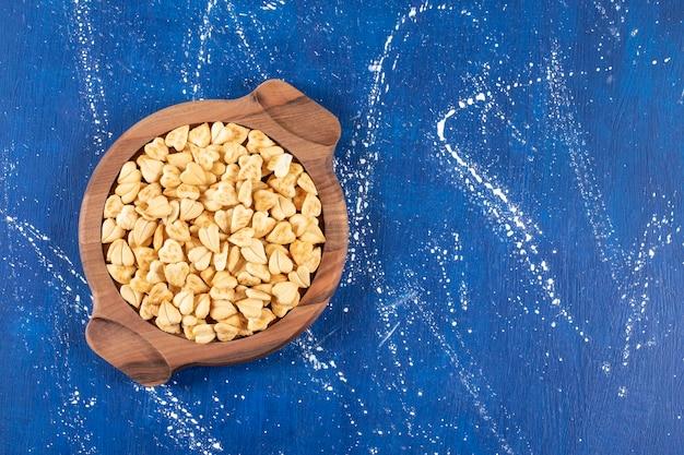 소금에 절인 하트 모양의 크래커 더미가 나무 판자 위에 놓여 있습니다.