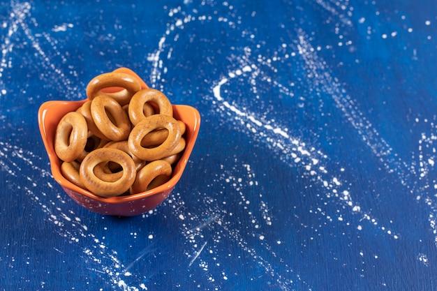 오렌지 그릇에 넣은 소금에 절인 둥근 프레즐 더미