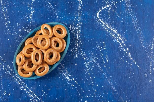 파란색 접시에 소금에 절인 둥근 프레즐 더미