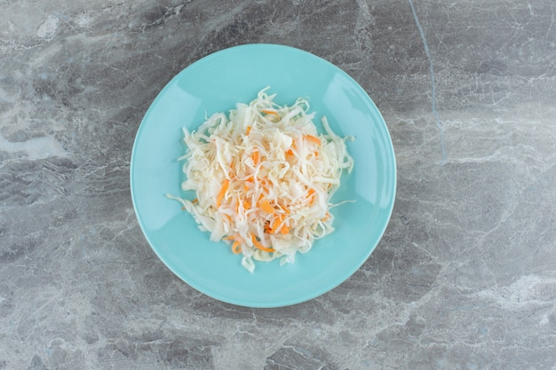 회색 위에 파란색 접시에 소금에 절인 양배추의 더미입니다.