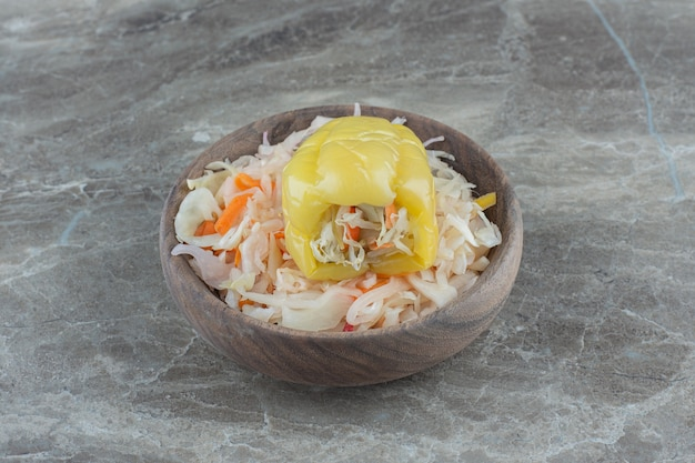 Куча квашеной капусты с перцем с начинкой в деревянной миске.