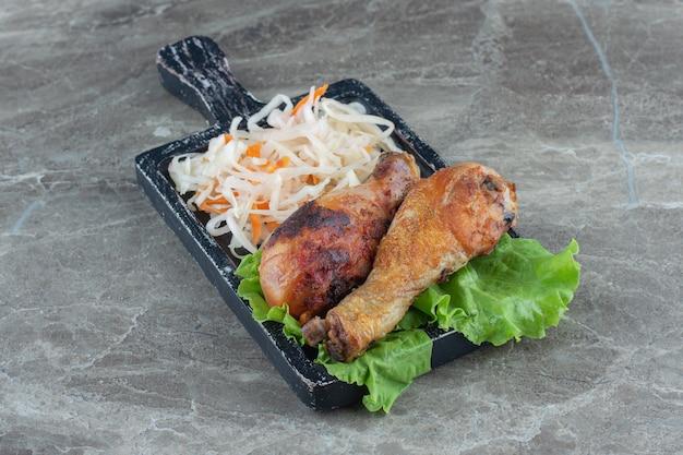 Куча квашеной капусты с жареными куриными ножками на деревянной доске.