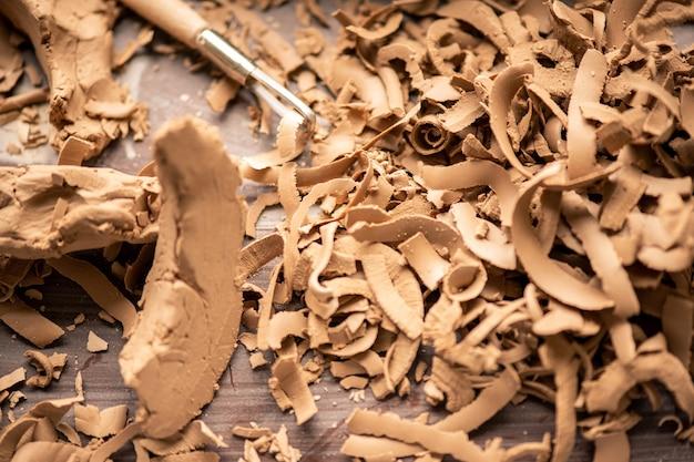 Куча стружек твердой глины на рабочем месте гончара после изготовления и обработки фаянса в мастерской