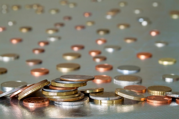 Куча блестящих монет разных размеров и цветов неравномерно уложены друг на друга. экономия денег и концепция финансового риска.