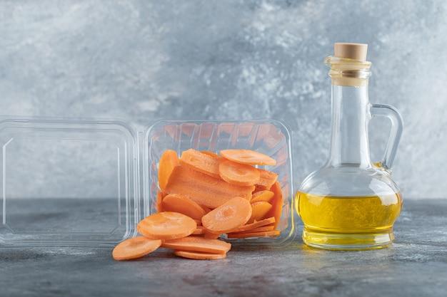 Куча нарезанной моркови в пластиковом контейнере и бутылке масла на сером фоне.