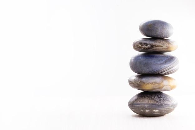 Куча спа-камней на столе на белой поверхности, копией пространства