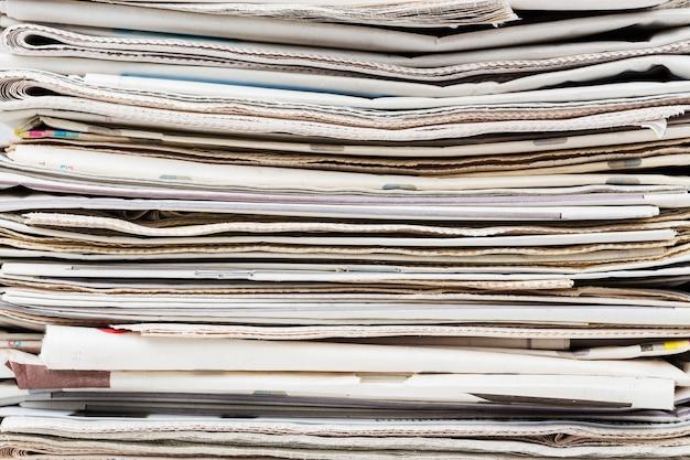 積み重ねられた一般的な折り畳まれた新聞の背景の山。ニュースとアップデートのコンセプト。