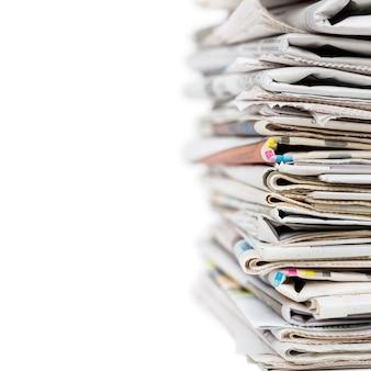 白い背景の上の積み重ねられた一般的な折り畳まれた新聞の山