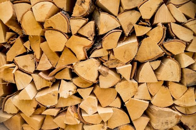 Готовая куча сложенных треугольных дров для камина и котла. сухие рубленые дрова готовы