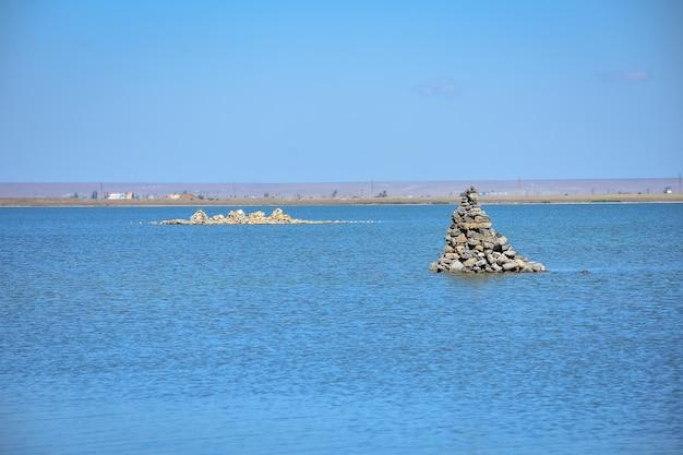 Куча камней посреди воды пирамиды из камней в озере