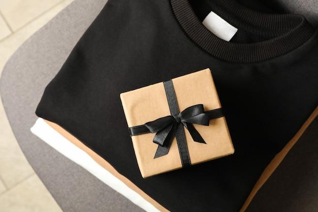 Куча стильных толстовок с подарочной коробкой на стуле