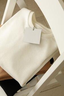 Куча толстовок на белом деревянном стуле