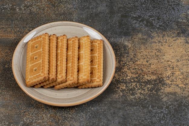 Куча вкусного печенья на керамической тарелке.
