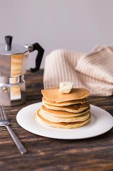 バターとおいしいパンケーキの山。朝食のコンセプト。