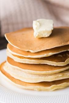 버터와 함께 맛있는 팬케이크의 더미입니다. 아침 식사 개념.