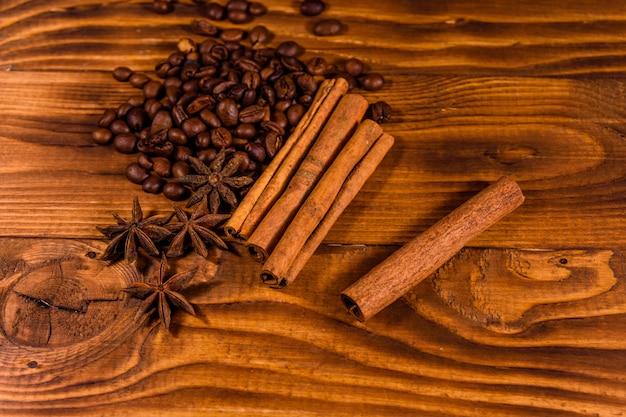 Куча кофейных зерен, звездчатого аниса и палочек корицы на деревенском деревянном столе