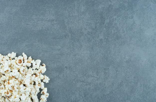 Куча вкусного попкорна на мраморном фоне. фото высокого качества