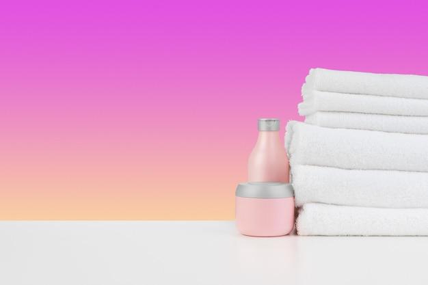 Куча бутылок для полотенец с шампунем на белом столе
