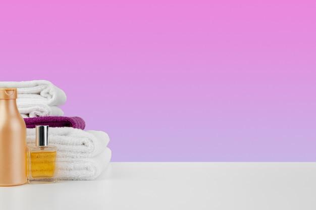 흰색 테이블에 샴푸가 있는 수건 병 더미