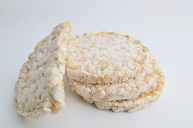 Куча два с половиной слоеных рисовых лепешек, изолированные на белом фоне. воздушный рисовый хлеб.