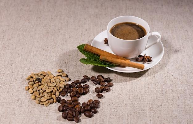 灰色のテーブルクロスの上にフルティーカップとソーサーの横にある2種類の異なる色のコーヒー豆の山