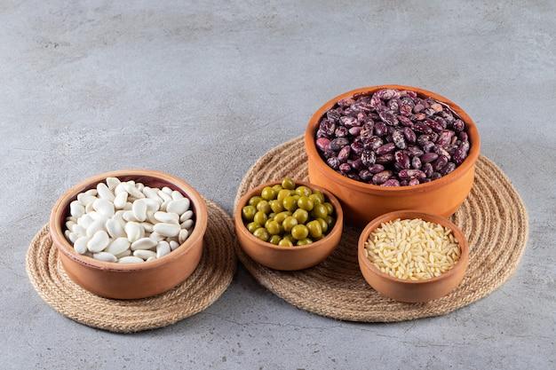 石の背景に未調理のレンズ豆、豆、米の山。