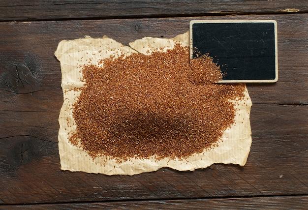 小さな黒板と未調理のテフ穀物の山