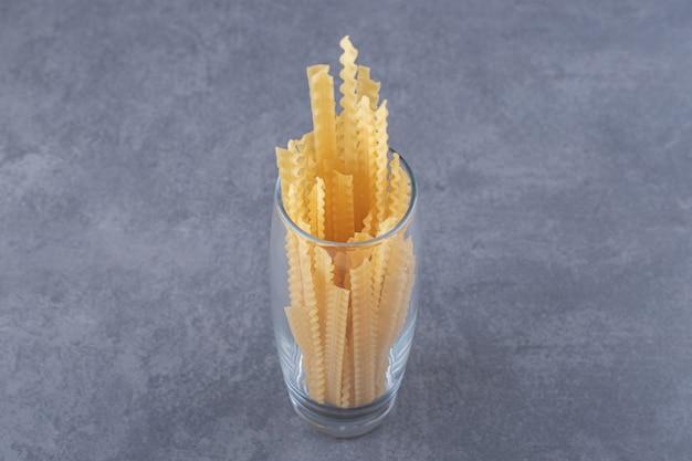 Куча сухих макаронных изделий различной формы в стекле.