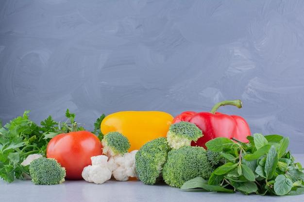 Куча овощей и зелени на мраморном фоне. фото высокого качества