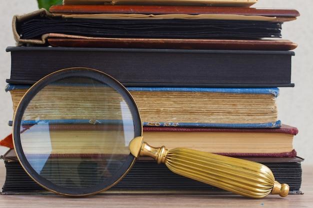 Куча старинных старых книг сложены на столе с зеркалом