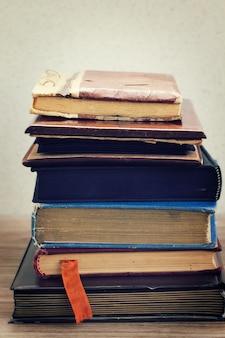 Куча старинных старых книг, сложенных на столе
