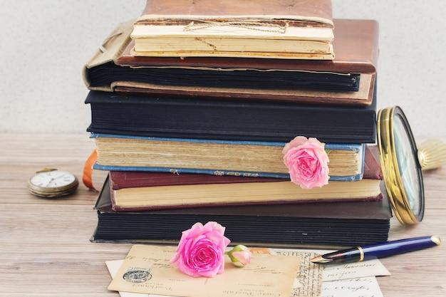 테이블에 장미 꽃 봉오리와 빈티지 메일이 쌓인 빈티지 오래된 책 더미