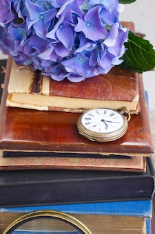 Куча старинных старых книг с синими цветами гортензии и старинными карманными часами