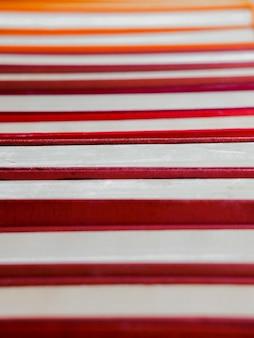 ハードカバーのヴィンテージ紙の赤い本の山。秋の読書リスト。