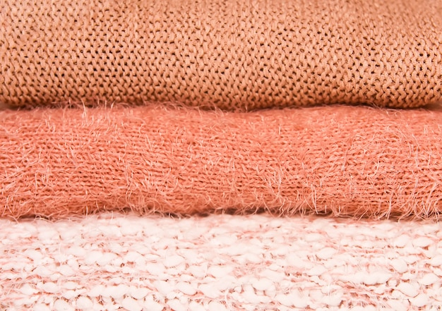家庭用ワードローブの棚に暖かい秋と冬のニットセーターの山。生きている珊瑚の色合いの服。