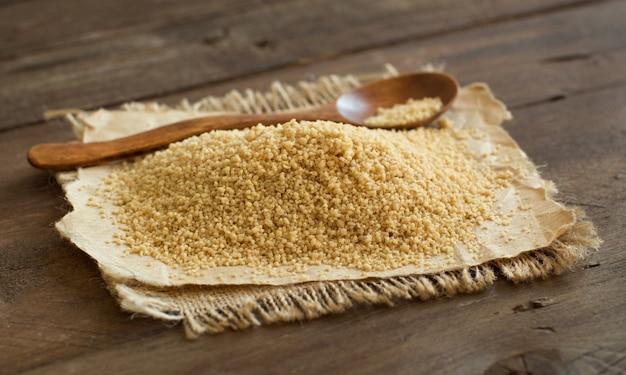 Куча кус-кус цельной пшеницы с ложкой на деревянном столе крупным планом