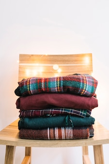 Pile of winter sweaters on wooden chair