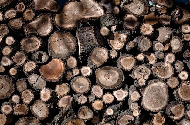 서로의 위에 함께 쌓인 나무 통나무 더미. 누적 된 나무의 벽을 배경으로 기록합니다. 목재 질감