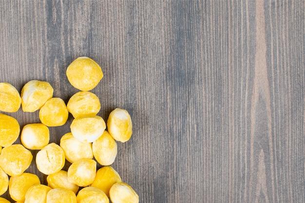 木製の表面に黄色いキャンディーの山