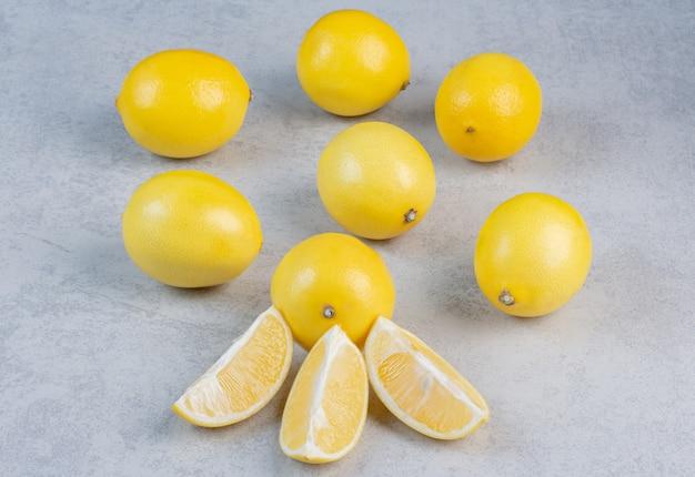 Куча желтого свежего лимона на сером фоне.
